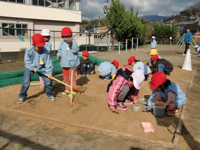 砂場でひろった貝殻を見せる橋本幼稚園の園児