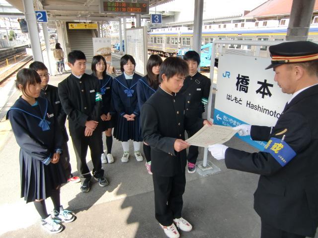JR橋本駅に手縫い座布団を取り付ける橋本中の生徒たち