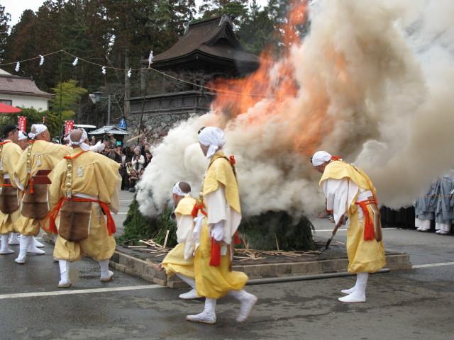 燃え盛る護摩壇の火に次々とお札を投げ込む山伏たち