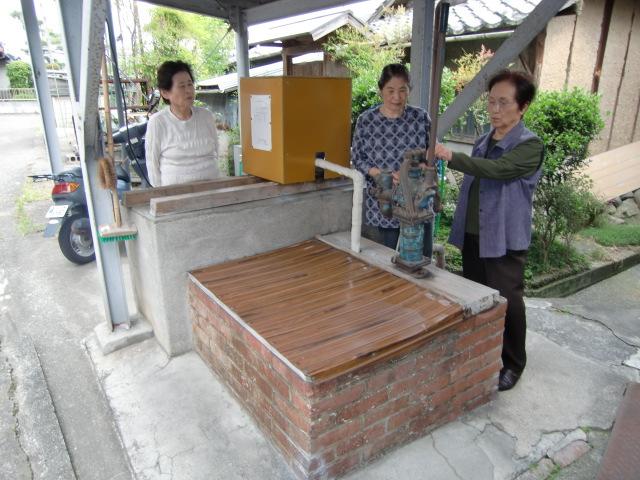 大地震でも大丈夫と古井戸のまわりで話す近所の人たち