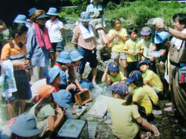 子どもたちと一緒に水生生物の調査をする会員たち