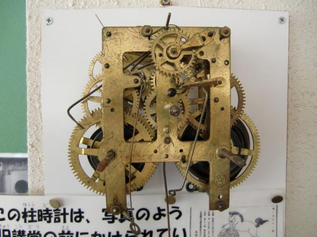 古い柱時計のネジを巻く児童ら