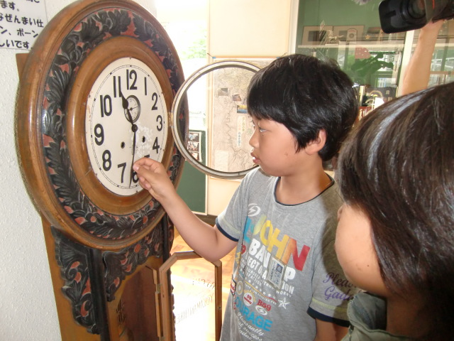 児童ら古い柱時計のネジ巻き~時の大切さ学ぶ