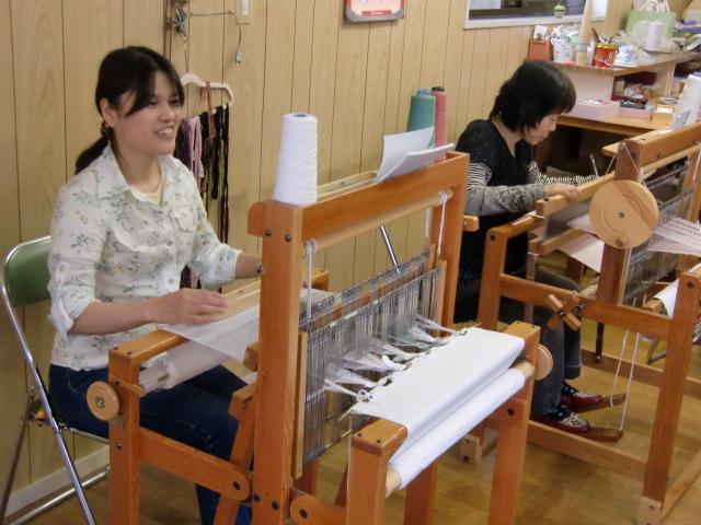 手機を使ってオリジナルな手織りを楽しむ女性たち