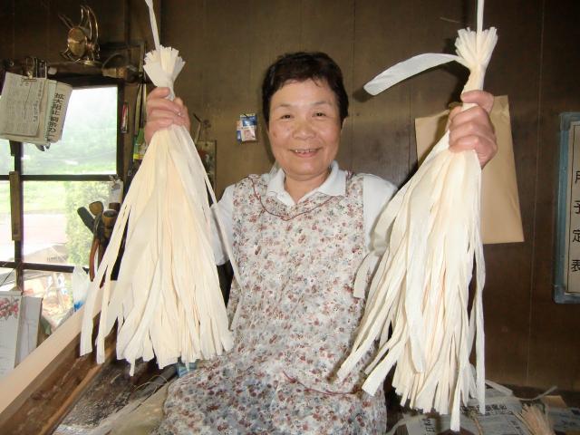 柳さんが鉋で削り取る桧紐を受け取り束にしていく昌子さん