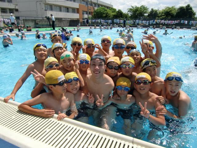 紀見小学校のプールで中村先輩と一緒に記念撮影する児童たち