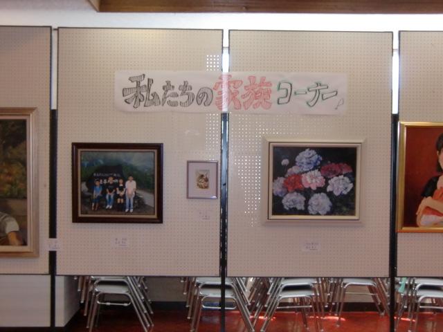 ほのぼのと家族が描かれた作品に見入る人たち