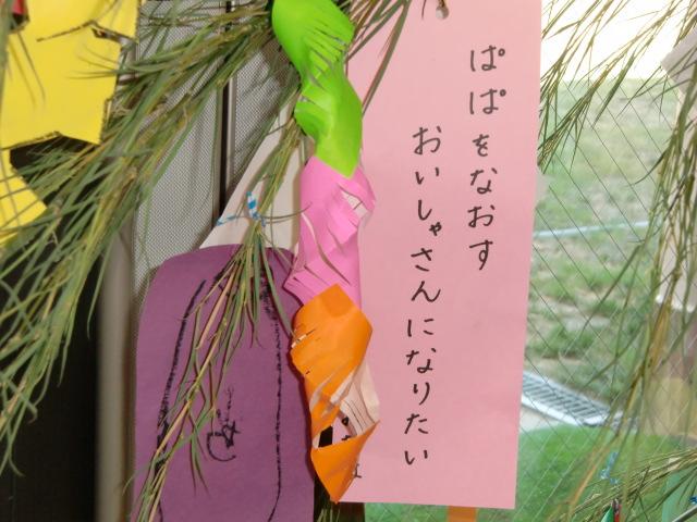 七夕飾りの下で英語の先生たちとともに園児らパチリ