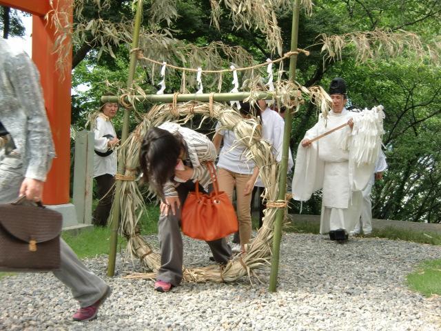 人々の幸せを祈り茅の輪をくぐる参拝者ら