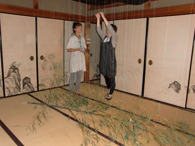 七夕飾りの短冊と同じように天と笹とを草木染め糸でつなぐ女性(左は秦さん)