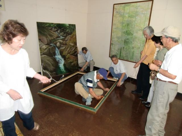市役所に絵画の掲示作業をする橋本絵画同好会の役員ら