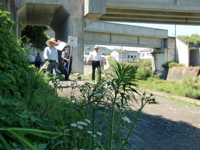 橋本川沿いに水難防止の看板を運ぶ地元住民ら