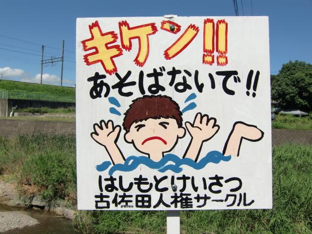 橋本川に水の事故注意の看板を立てる地元住民とお巡りさん