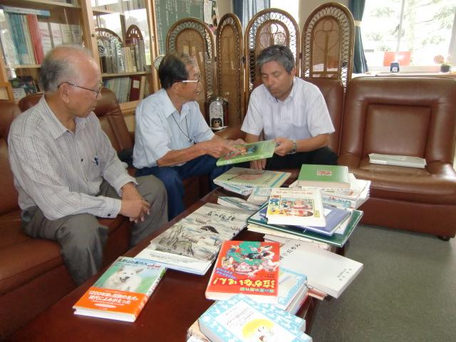 宮井校長(右)に図書寄贈する阪口(中)さんら