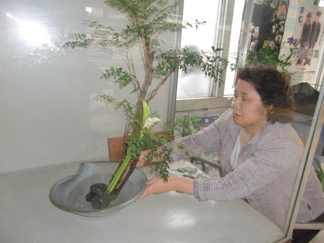 橋本駅の一角に海芋の花を生ける加隈さん