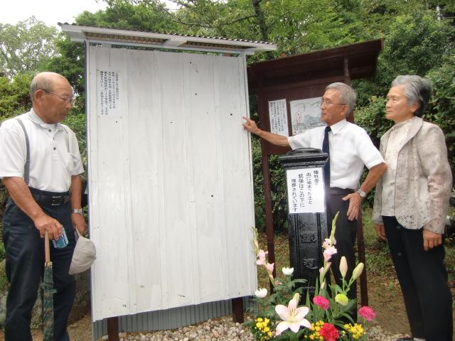 銃弾跡の残る板壁保存を喜ぶ(左から)恋中さん、平林さん、山本さん