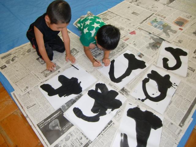 「わ」の文字を書く園児と見守る北村先生