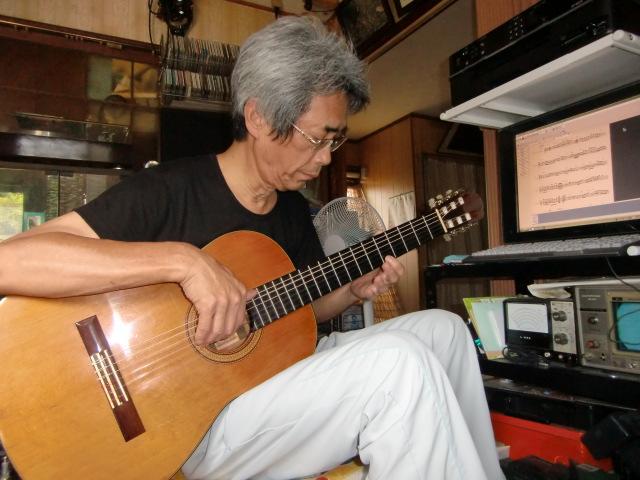 自ら作曲した演歌をギターで爪弾く世古さん(自宅で)