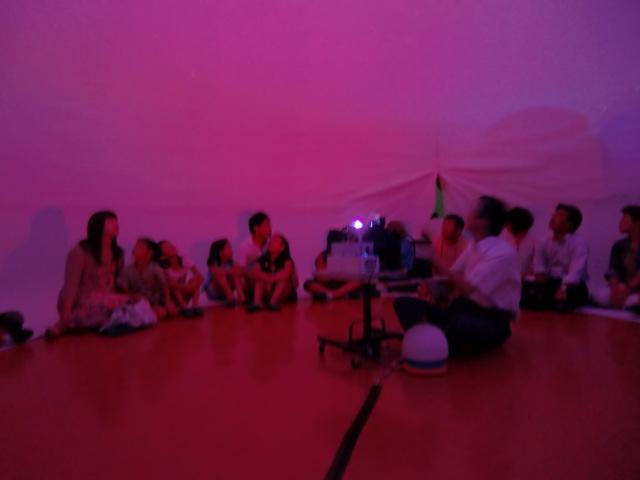 モバイルプラネタリウムのそばで山本会長の「宇宙」の話を聴く親子たち