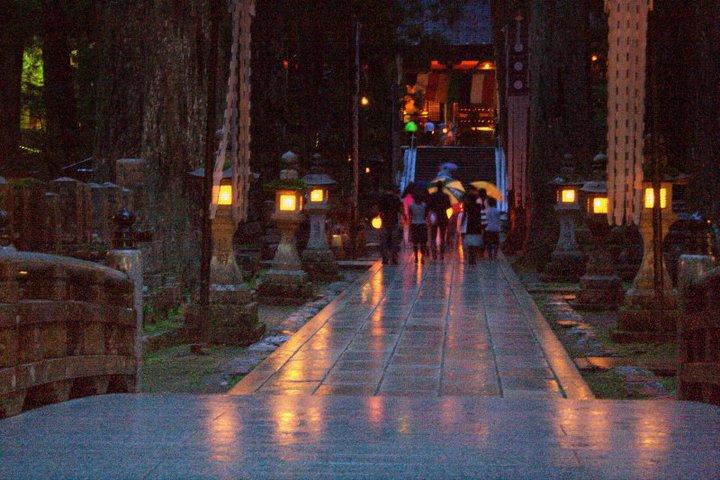 高野山の奥の院・表参道を提灯明かりであるく参加者ら