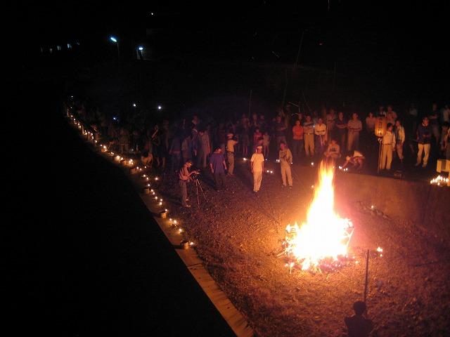 経木や棚を燃やす炎の周囲では人々がロウソクを灯し祈る