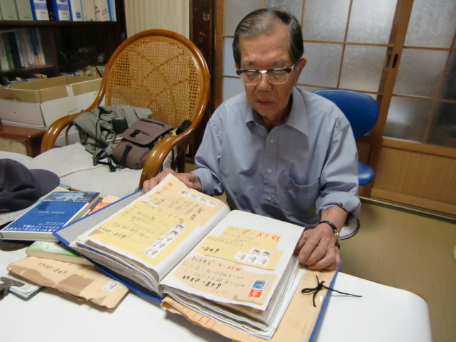 匿名・郵便物の封筒や切手をアルバムに貼り付け保存する阪口さん