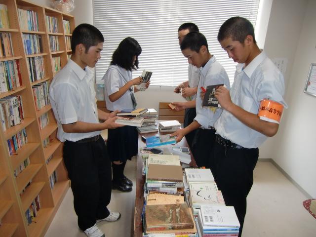 戦争文庫の本に「ゆかいな図書館」のゴム印を押す橋本高校野球部員ら