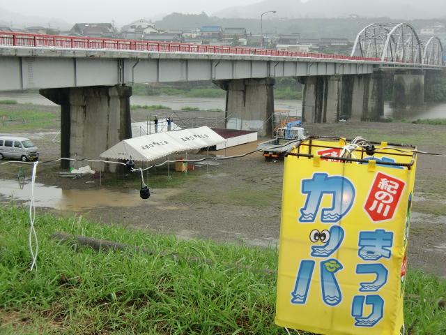大雨のなか九度山橋下の特設ステージを撤去する実行委メンバーら