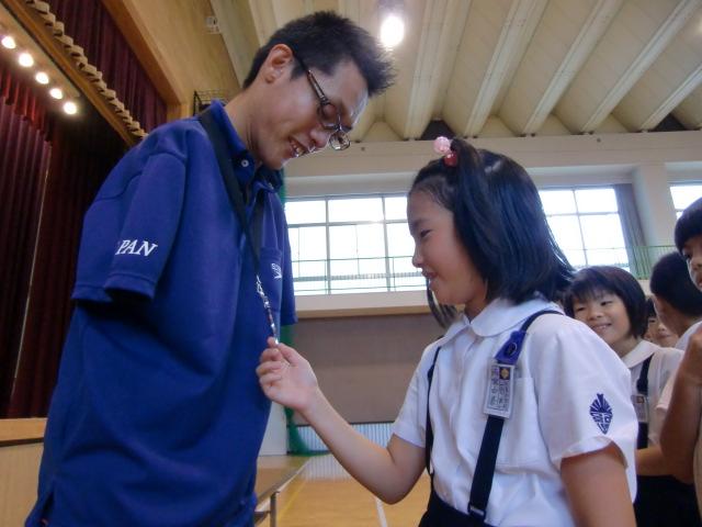 中村選手の首の銀メダルに触れる女子児童