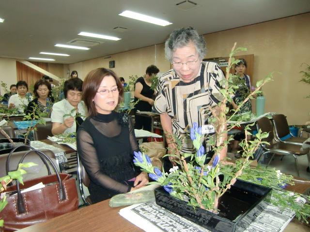 堀内師範(右)の生け花を静観する嵯峨御流の中野教授(左)