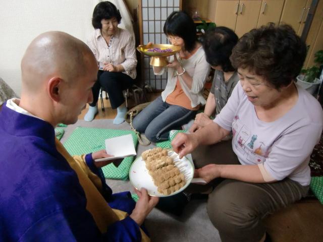菊酒をいただく女性(向こう)と団子を配る岩西住職(手前)