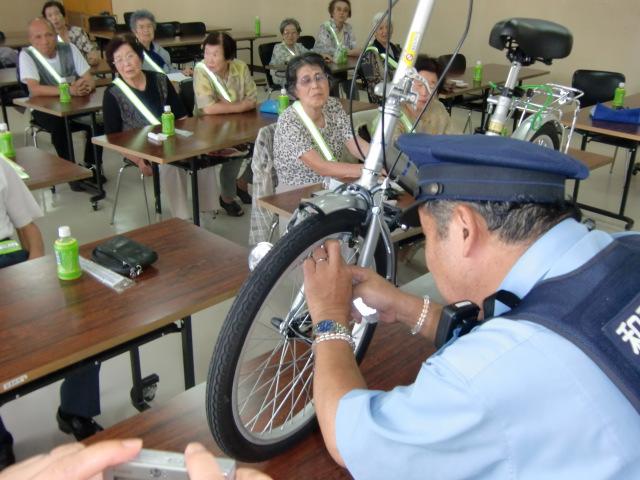 自転車のスポークへの反射材取り付け方を指導する岩戸所長