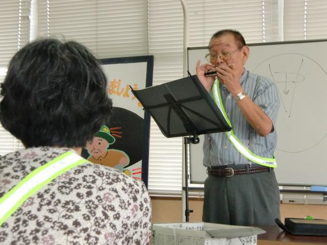お年寄りらにハーモニカで「月の砂漠」を演奏する澤田さん