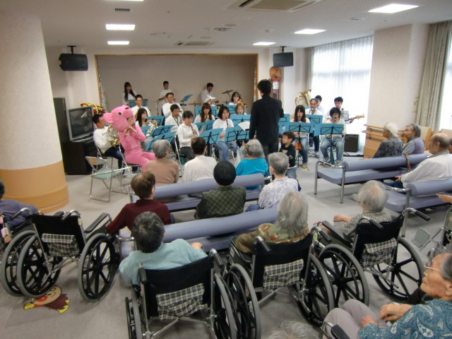 施設のお年寄りらに心を込めて管楽器を演奏する団員たち