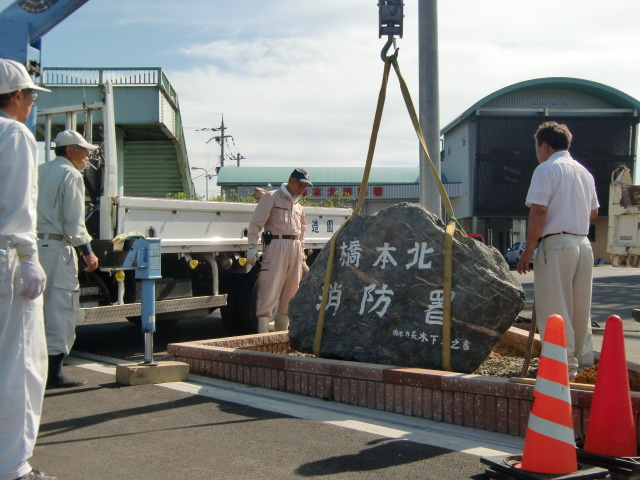 橋本北消防署に自然石の看板を設置する「一世の会」会員ら