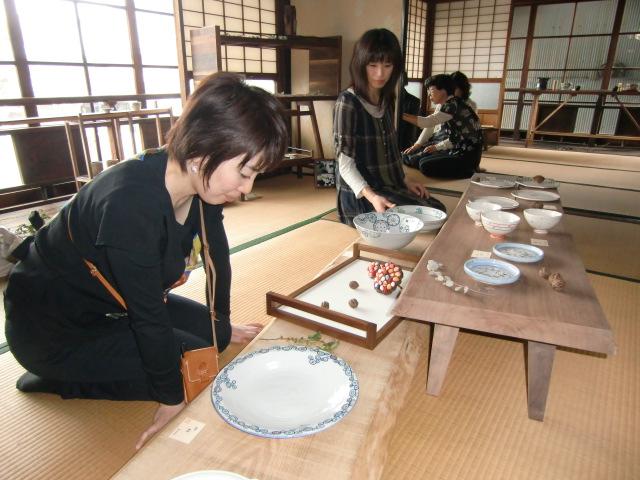 五福大さん(左)制作の飾り棚の前で自作の水差しを披露する妻香菜子さん