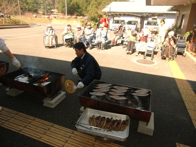 施設のお年寄りの前で秋刀魚などを炭火焼きする南陽食品の木村専務