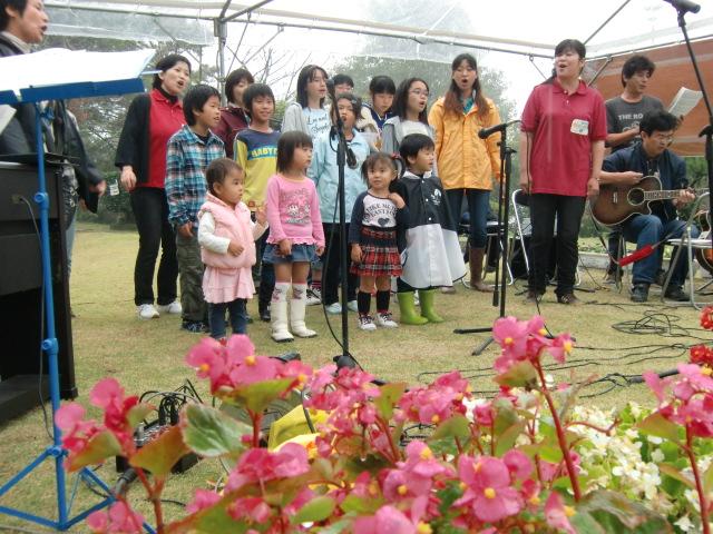合唱集団「ことだま」と一緒に歌う子供たち(雨の杉村公園で)