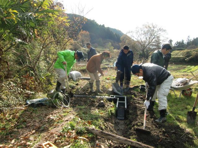 水田魚道を設置する三塚さんや佐藤さんたち